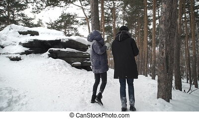 Two people are walking in winter forest trail