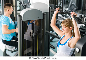 Two people at fitness center exercise machine - Active man...