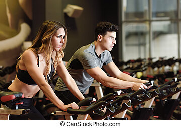 Couple in a spinning class wearing sportswear. - Two people...