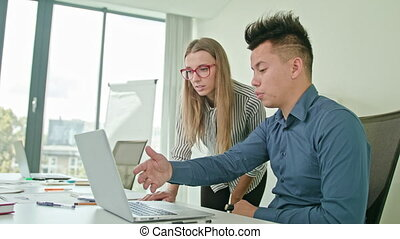 Two People Discussing Ideas Using Laptop