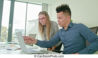 Two People Discussing Ideas Using Laptop - Two people in...