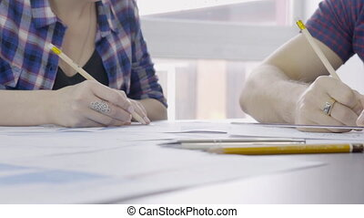 Two people draw a drawing on ruler with a pencil on the...