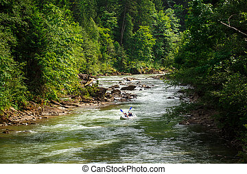 two people floating in a canoe on a mountain river