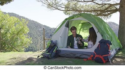Young laughing couple sitting in tent and drinking tea while taking rest in mountains.