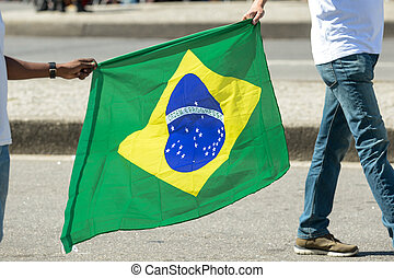two people holding the brazilian flag.