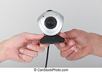Two people holding webcam