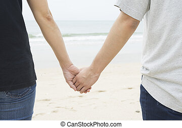 Two people holdong hands together