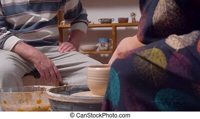 Two people in a pottery workshop. A man watches how a woman ...