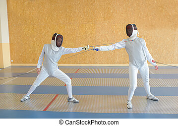 Two people in fencing combat