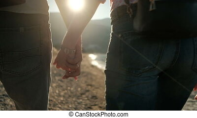 Two people in jeans walk along the rocky seashore to hold hands.