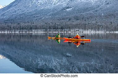 two people kayaking in the winter among mountains - two ...
