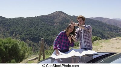 Two people looking at map searching route - Two young people...