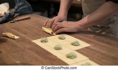 Two people making tortellini traditional Italian food -...