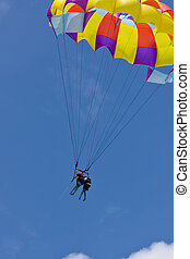 Two people parasailing against blue sky