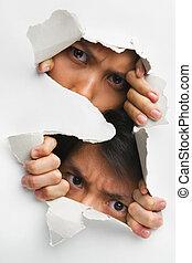 Two people peeking from hole in wall