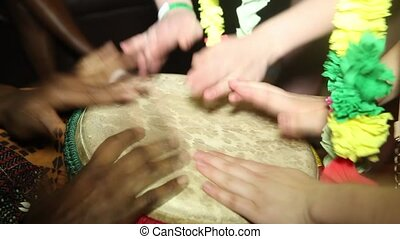 Two people playing on Jambe Drum no face. Closeup of man's hands drumming out a beat on an African skin-covered djembe hand drum.