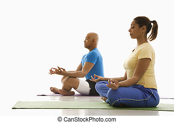 Two people practicing yoga. - Side view of mid adult...