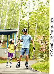 two people rollerblade. Dad with his little daughter on the...