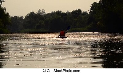 Two people rowing along the river with paddles sitting in a kayak are sent to sunset. Slow motion