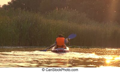Two people rowing oars sitting in a kayak on the lake in the sunset