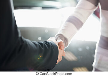 Two people shaking hands in a sunny place