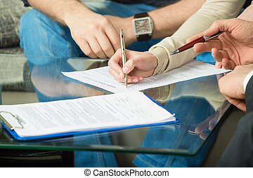 Two people signing a document - Hands of people signed the...