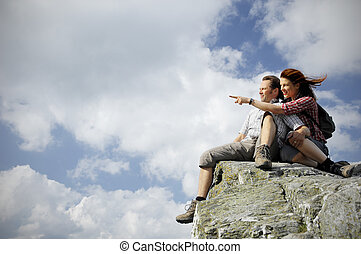 Two people sitting on top of a mountain, woman pointing towards something in the distance