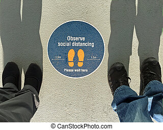 Two people standing beside Observe social distancing sign