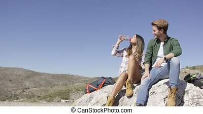 Two people taking rest on stone - Young man and woman ...