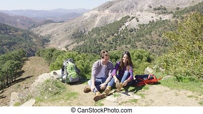 Two people taking rest while hiking - Two young people...