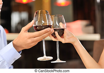 Two people toasting with wine glasses. young couple drinking...