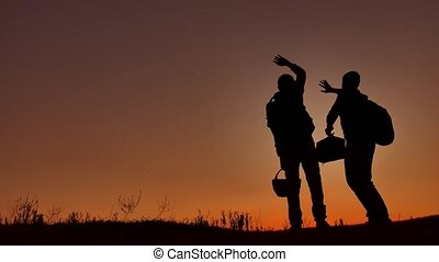 Two people tourists call for help silhouettes of the...