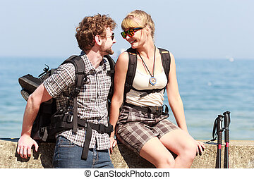 Two people tourists hiking by sea ocean.