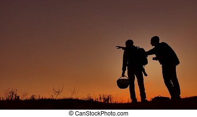 Two people tourists silhouette at sunset. Dawn travel...