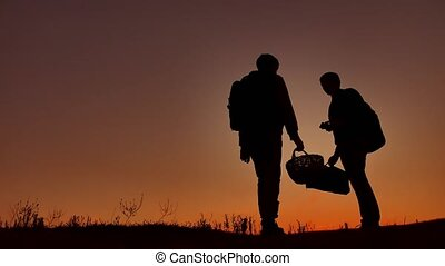 Two people tourists silhouette at sunset. Dawn sunrise sunlight tourist travel boy and man