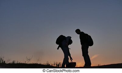 Two people tourists travel silhouette at sunset. Dawn sunrise sunlight tourist boy and man