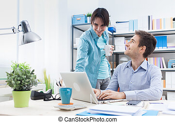 Two people using a computer in the office