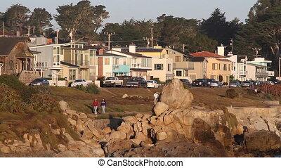 two people walk near rocky shoreline