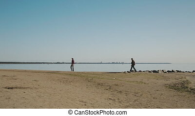 two people walk on the beach.