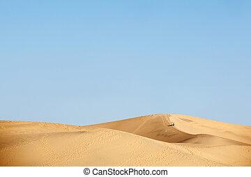 two people walking in desert dunes - two people walking in...