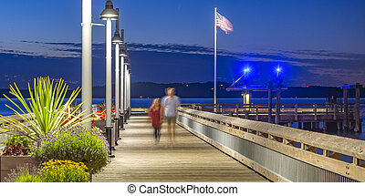 Two people walking on the Tacoma pier at sunset