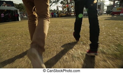 Two people walking to a funfair - A hand held close up shot...