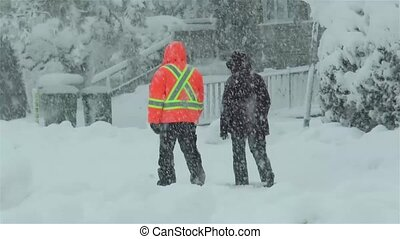 Winter season: two people walk on a snow covered sidewalk under intense snowfall.
