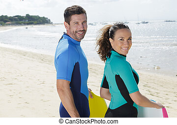 two people with bodyboards