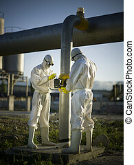 Two people with masks maintaining gas tubes
