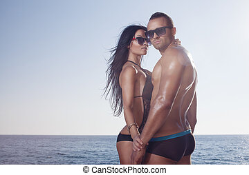 Two perfect bodies person posing on sea background. Male and...