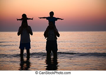 Two person in sea with children on shoulders
