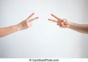 Two person playing rock paper scissors with both posturing scissors symbol on white background.