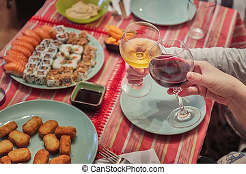 Two persons cheers in a table dinner with sushi and fried ...