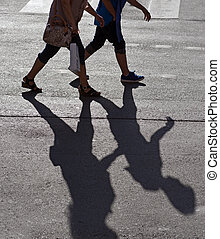 Two persons crossing street - Shadow of two back lit people ...